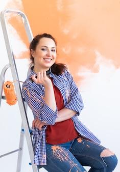 Mulher sorridente, pintando a parede interior da casa. conceito de renovação, reparação e redecoração.