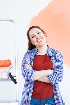 Mulher sorridente pintando a parede interna da casa