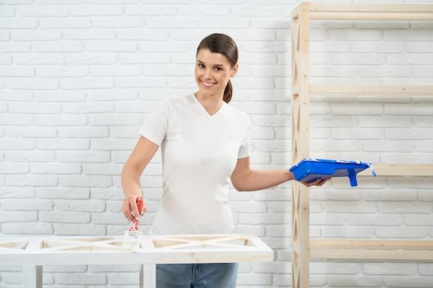 Mulher sorridente pintando com pincel prateleiras de madeira