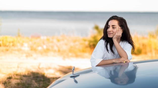 Mulher sorridente posando à beira-mar