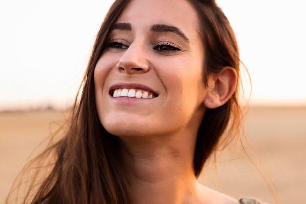 Mulher sorridente posando ao ar livre ao pôr do sol