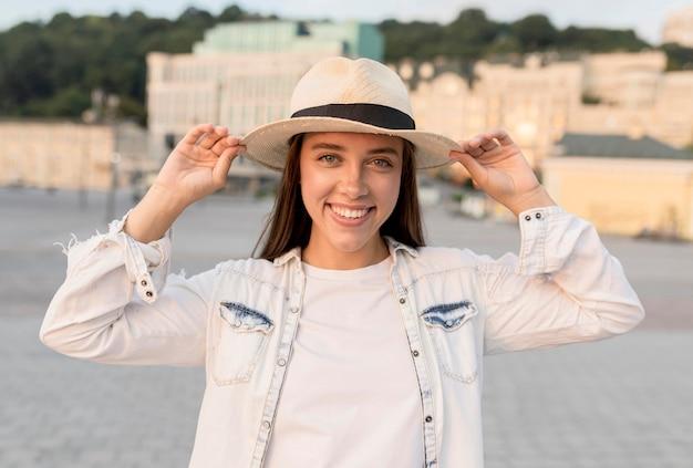 Mulher sorridente posando ao ar livre com chapéu enquanto viaja