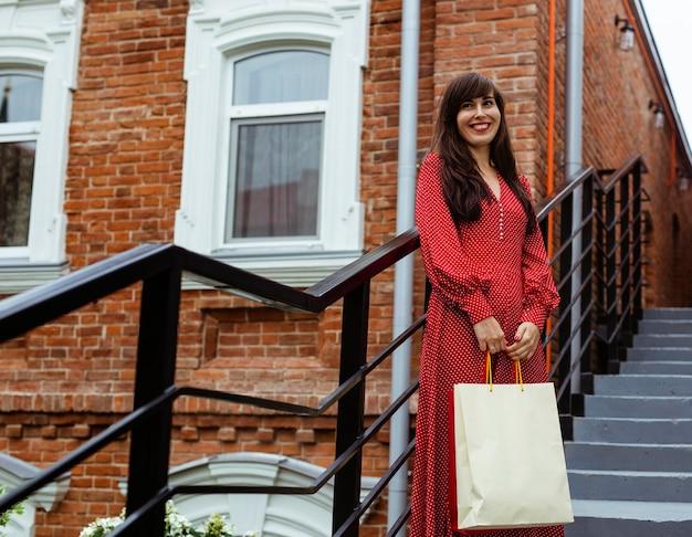 Mulher sorridente posando ao ar livre com sacolas de compras