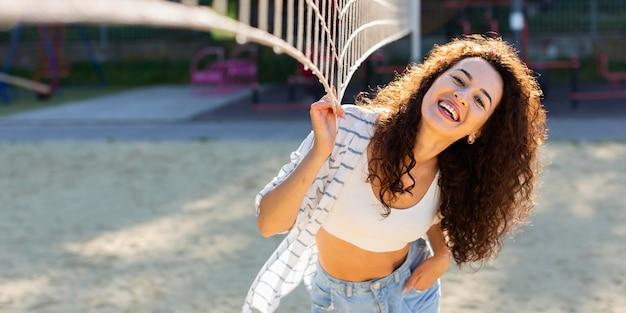 Mulher sorridente posando ao lado de um campo de vôlei com espaço de cópia
