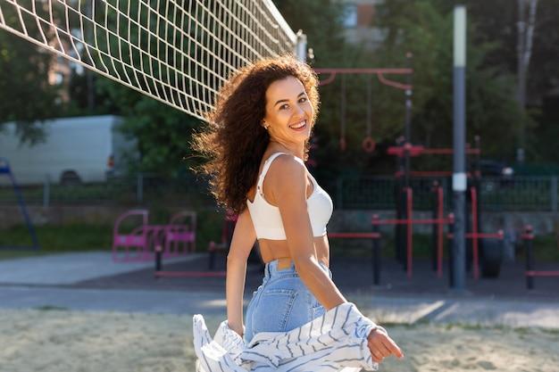 Mulher sorridente posando ao lado de um campo de vôlei do lado de fora