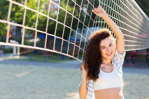 Mulher sorridente posando ao lado de um campo de vôlei