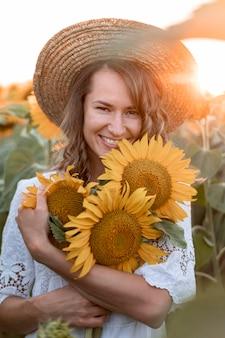 Mulher sorridente posando ao pôr do sol