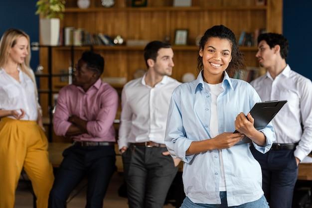 Mulher sorridente posando com a prancheta e colegas de trabalho