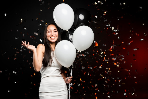 Mulher sorridente posando com balões na festa de ano novo