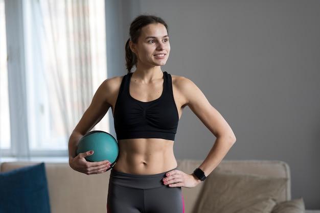 Mulher sorridente posando com bola medicinal