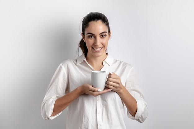 Mulher sorridente posando com caneca