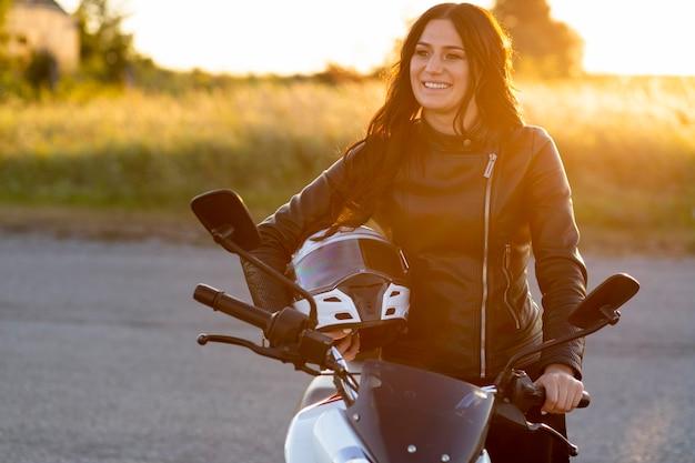 Mulher sorridente posando com capacete em sua motocicleta