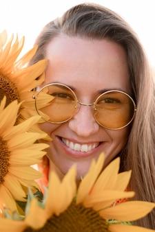 Mulher sorridente posando com girassóis