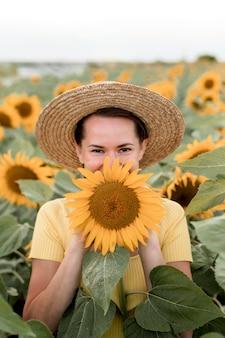 Mulher sorridente posando com girassol