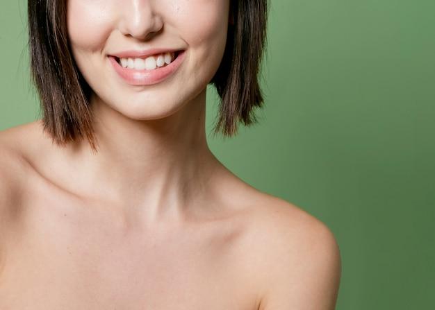 Mulher sorridente posando com ombros nus