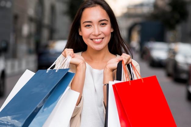 Mulher sorridente posando com sacolas de compras após a compra da venda