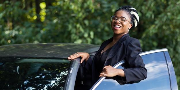 Mulher sorridente posando com seu carro novo