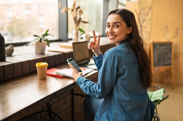 Mulher sorridente posando com smartphone em um café enquanto espera por um amigo.