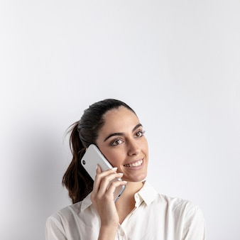 Mulher sorridente posando com smartphone
