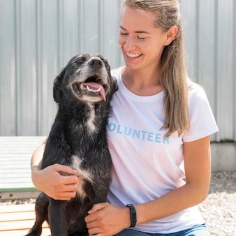 Mulher sorridente posando com um cachorro fofo de resgate