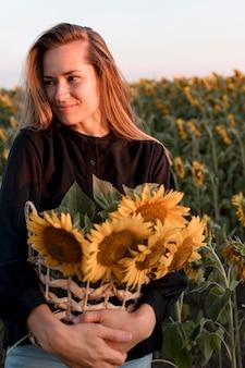 Mulher sorridente posando com uma cesta de girassóis