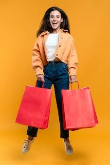 Mulher sorridente posando enquanto pula e segura sacolas de compras
