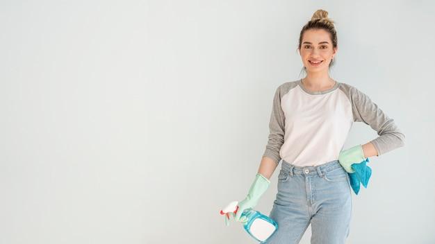 Mulher sorridente posando enquanto segura a solução e pano de limpeza