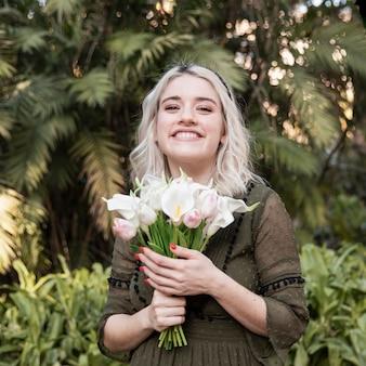 Mulher sorridente posando enquanto segura o buquê de flores