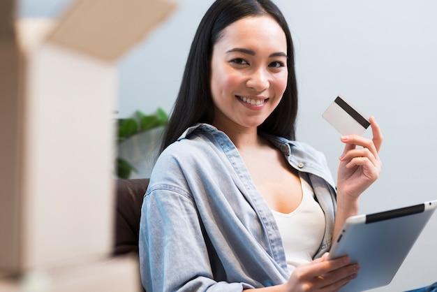 Mulher sorridente posando enquanto segura o cartão de crédito e tablet