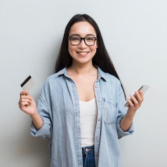 Mulher sorridente posando enquanto segura o smartphone e cartão de crédito