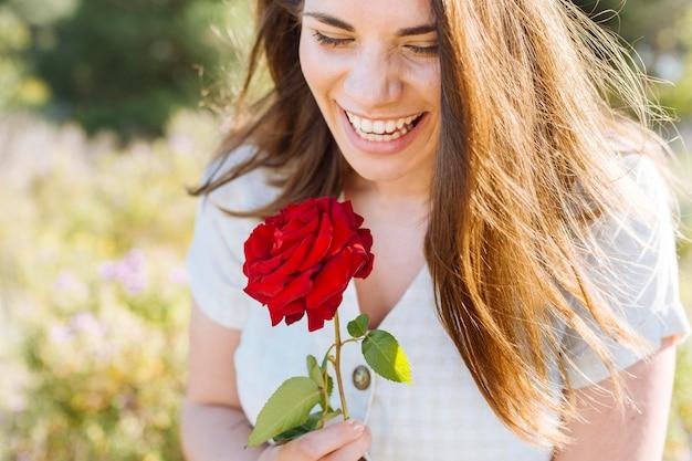 Mulher sorridente posando enquanto segura rosa