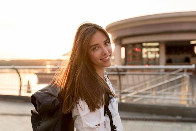 Mulher sorridente posando enquanto viaja sozinha