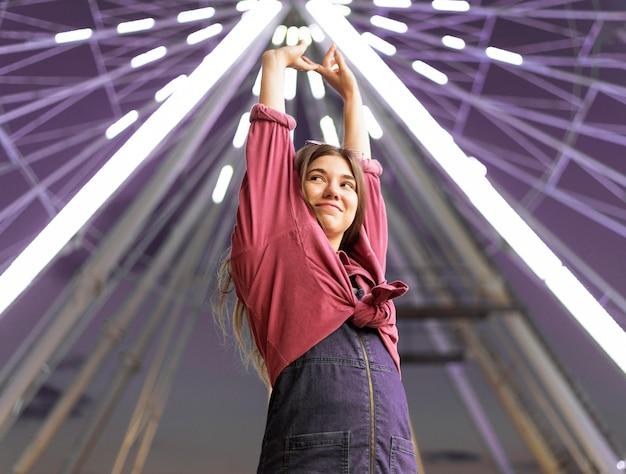 Mulher sorridente posando no parque de diversões ao lado da roda gigante