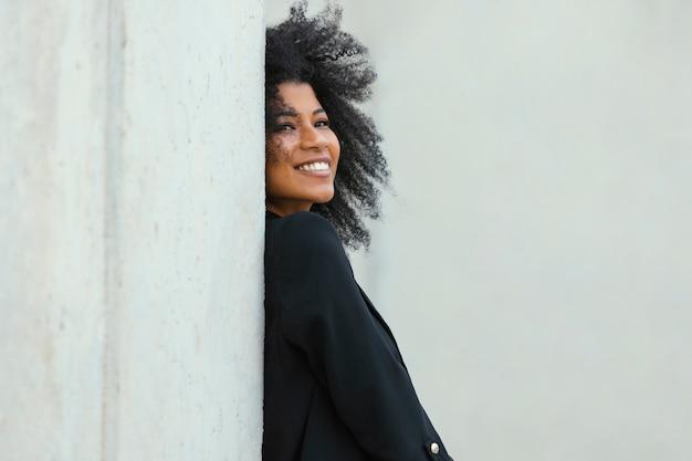 Mulher sorridente posando perto de parede foto média
