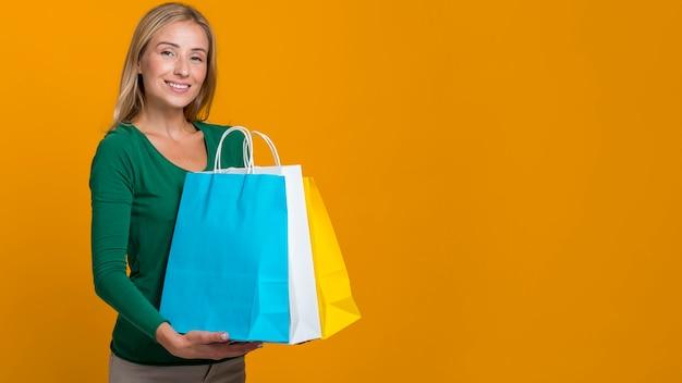 Mulher sorridente posando segurando várias sacolas de compras com espaço de cópia