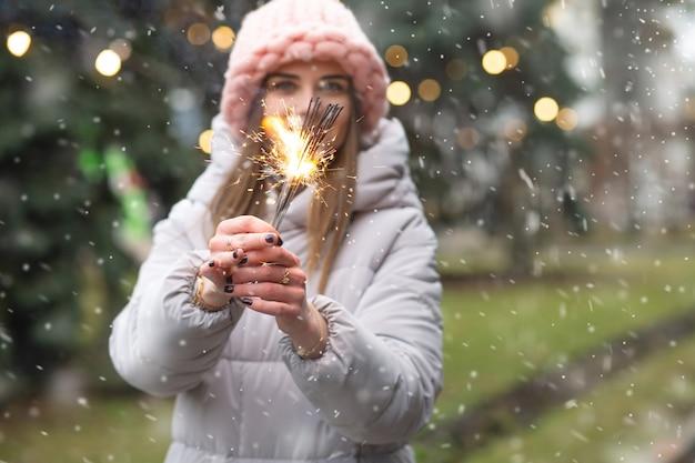 Mulher sorridente positiva se divertindo com estrelinhas perto da árvore do ano novo durante a queda de neve