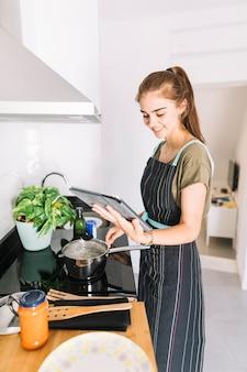 Mulher sorridente, preparando alimento, segurando, tablete digital
