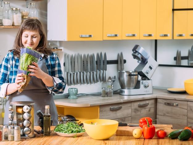 Mulher sorridente preparando legumes na cozinha