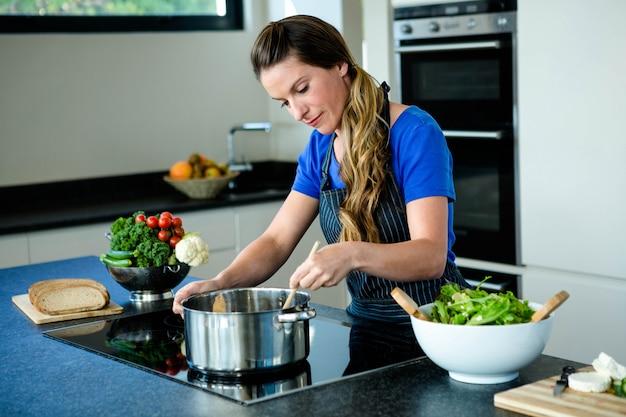 Mulher sorridente preparando legumes para o jantar em um fogão