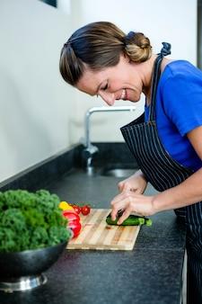 Mulher sorridente preparando legumes para o jantar em uma tábua de madeira