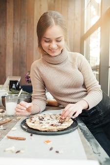 Mulher sorridente preparando torta de natal na cozinha