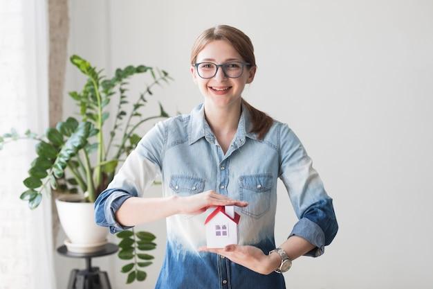 Mulher sorridente, protegendo o modelo de casa no escritório olhando para a câmera