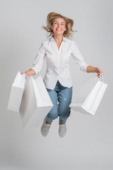 Mulher sorridente pulando e posando enquanto segura várias sacolas de compras