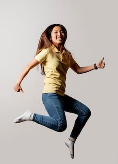 Mulher sorridente pulando no estúdio