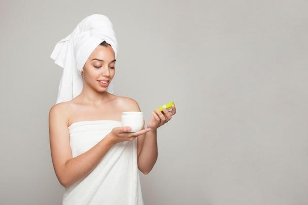 Mulher sorridente que abre o produto cosmético