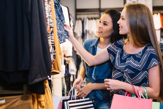 Mulher sorridente que explora a loja de roupas