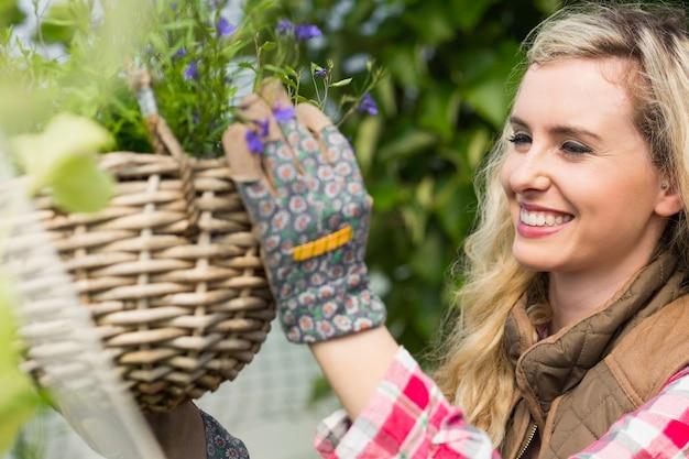 Mulher sorridente que repara uma cesta de flores pendurada