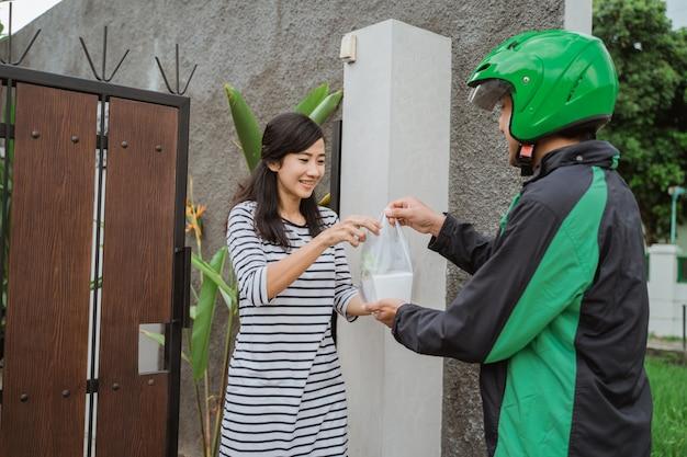 Mulher sorridente, recebendo a entrega de compras em casa