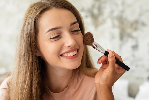 Mulher sorridente recebendo ajuda de um amigo para se maquiar