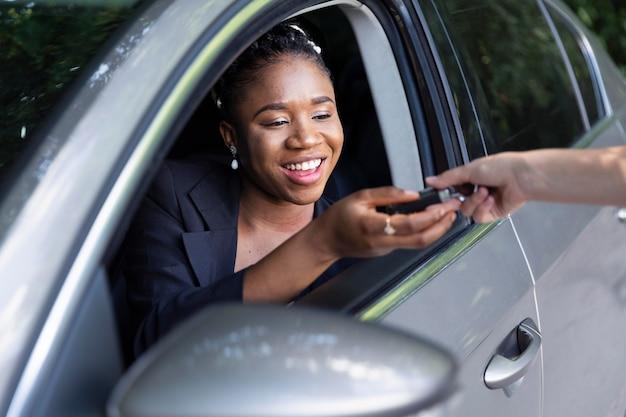 Mulher sorridente recebendo as chaves de seu carro novo